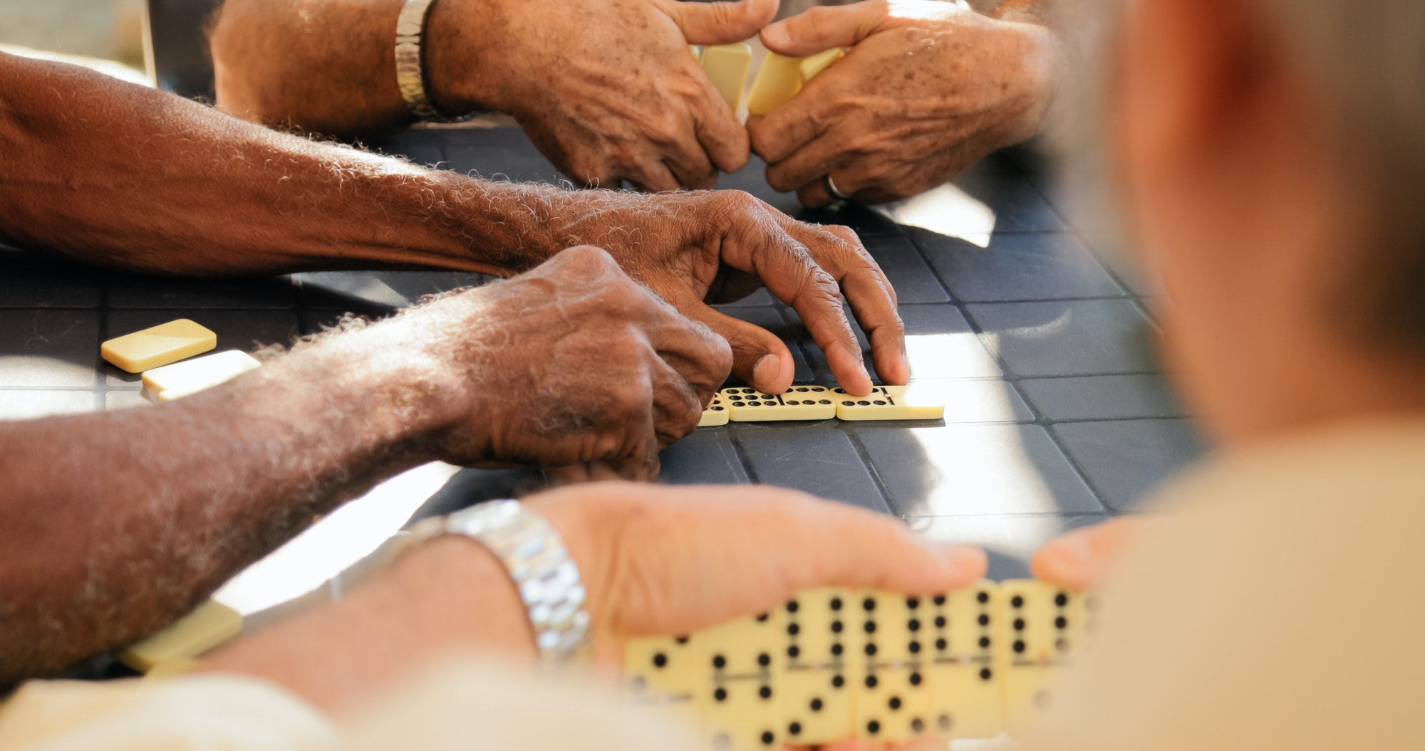 retired old men playing domino game with friends - ASSIN Brasil